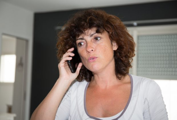 Smiling happy brunette woman talking on mobile phone